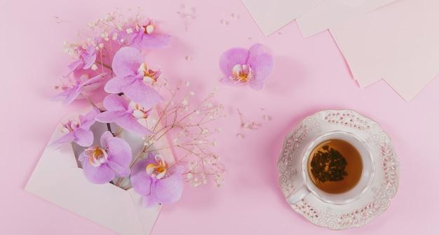 Zarte überkopfkomposition mit morgendlicher tasse tee, rosa brieftasche voller lila orchideenblüten und leerem umschlag auf hellrosa oberfläche