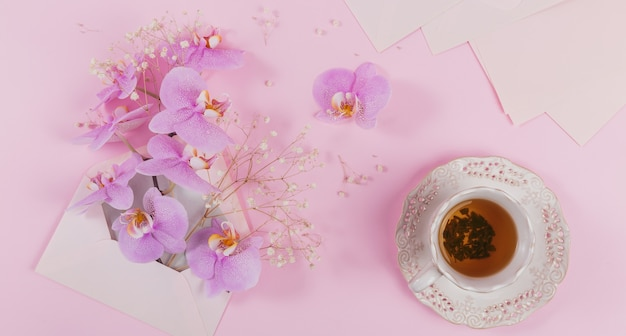 Zarte überkopfkomposition mit morgendlicher tasse tee, rosa brieftasche voller lila orchideenblüten und leerem umschlag auf hellrosa