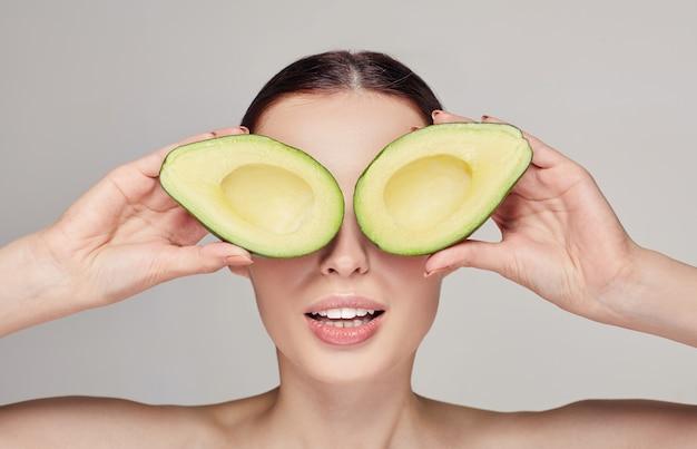 Zarte überraschte dame mit avocadogläsern