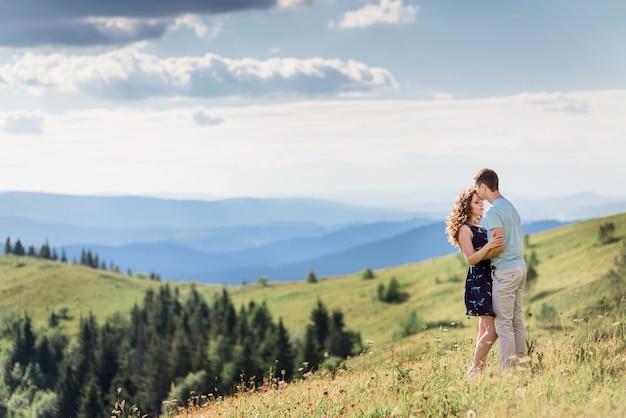 Zarte umarmungen eines paares, das auf einem grünen hügel vor herrlicher landschaft steht