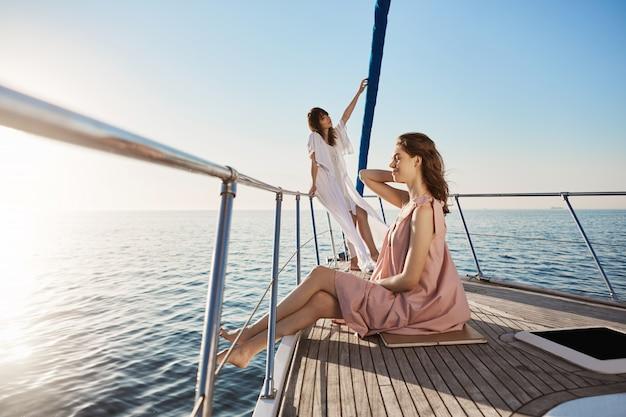 Zarte und attraktive erwachsene frau, die zeit auf dem boot verbringt. frau steht auf trug der yacht mit verträumtem blick, während ihre freundin an der seite sitzt, beide fühlen sich wie im paradies