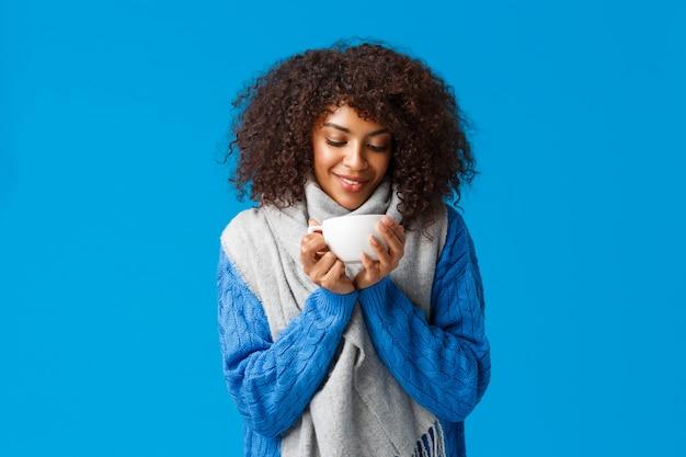 Zarte und niedliche afroamerikanische frau mit afro-haarschnitt, im pullover und im schal, die heißen köstlichen tasse tee betrachten, lächelnd und genießen komfort und gemütlichkeit des winterskigebiets, blauer hintergrund