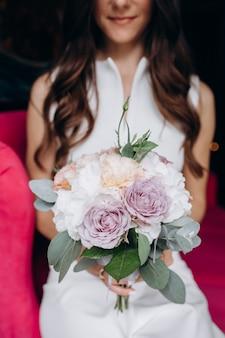 Zarte und reizende braut sitzt mit reichem hochzeitsblumenstrauß auf einer rosa couch im café