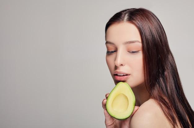 Zarte und ruhige dame mit der avocado in der hand, die unten schaut