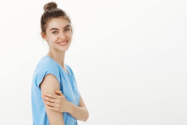 Zarte und weibliche lächelnde frau, die glücklich schaut