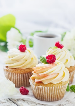 Zarte vanille-cupcakes mit sahne und himbeeren auf weißem holz