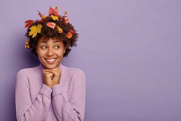 Zarte weibliche frau hält hände unter dem kinn, drückt positive gefühle nach dem herbstspaziergang aus, hat laub in lockigem haar in pullover gekleidet