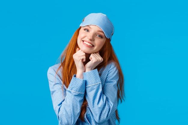 Zarte, weibliche rothaarigefrau mit toothy schönem lächeln, neigungskopf, der arme nahe der reizenden haltung des gesichtes hält und als stellung in der nachtzeug- und schlafmaske lächelt, bereiten haben süße träume, blaue wand vor