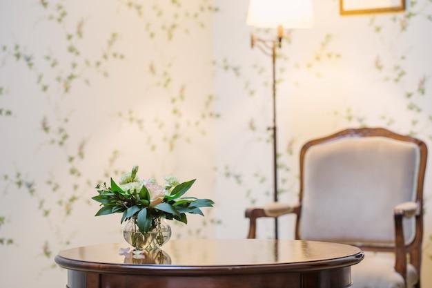 Zarter blumenstrauß in glasvase im vintage-interieur