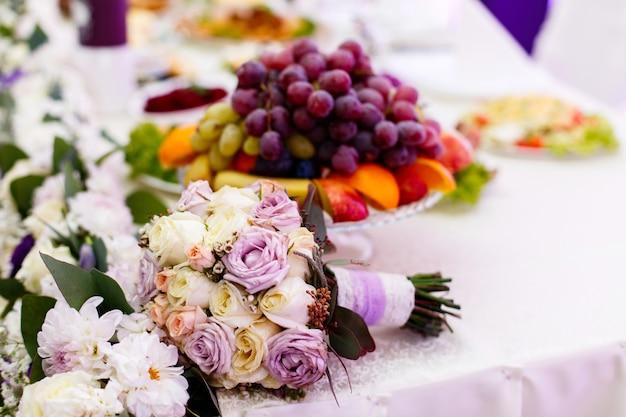 Zarter hochzeitsblumenstrauß aus beige und violetten rosen