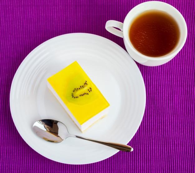 Zarter quark-dessert-souffle-kuchen mit gelee-kiwi auf einem weißen teller auf serviette und tasse tee. die draufsicht