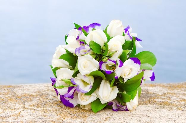 Zartes brautstrauß aus lila eustomas und weißen rosen