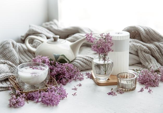 Zartes frühlingsgesteck mit blumen in einer vase, einem glas milch und wohndeko-details