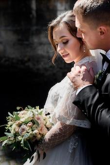 Zartes hochzeitspaar umarmt, porträt des bräutigams und der braut im freien mit hochzeitsstrauß, heiratskonzept