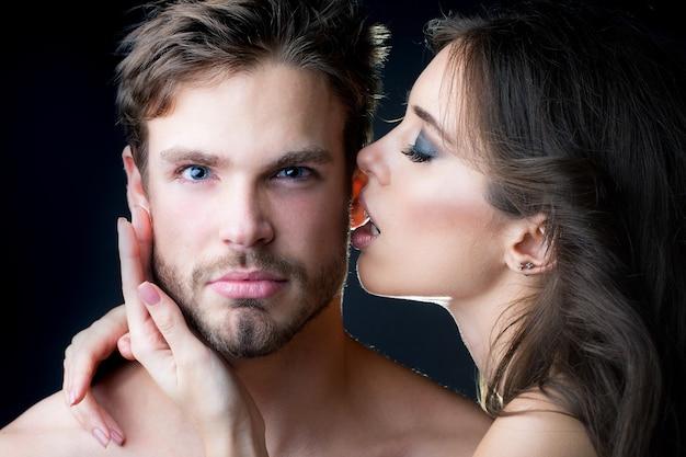 Zartes junges paar, das nahaufnahmeporträt des jungen schönen sexuellen paares der sexy frau mit dem umarmen und küssen des gutaussehenden mannes im studio auf schwarz küsst