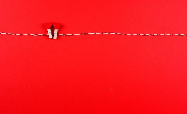 Zartes kleines herzsymbol des valentinstags auf einer kreativen postkarte der wäscheklammer und der schnur, kopienraum, flach lag auf rotem hintergrund