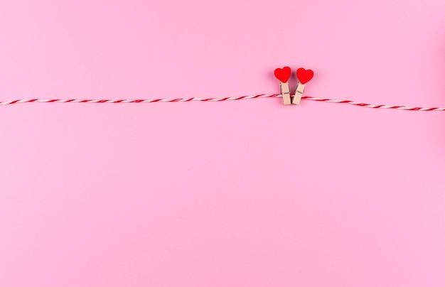 Zartes kleines herzsymbol des valentinstags auf einer kreativen postkarte von wäscheklammer und schnur, kopienraum, flach lag auf rosa hintergrund