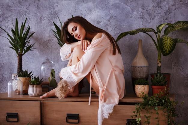 Zartes mädchen in einem nachthemd sitzt auf einem nachttisch. ihre augen sind geschlossen und sie lächelt