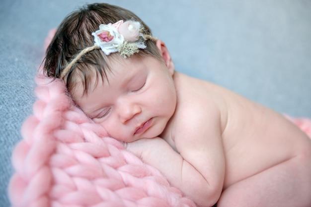 Zartes neugeborenes, das mit kranz auf kopf schläft