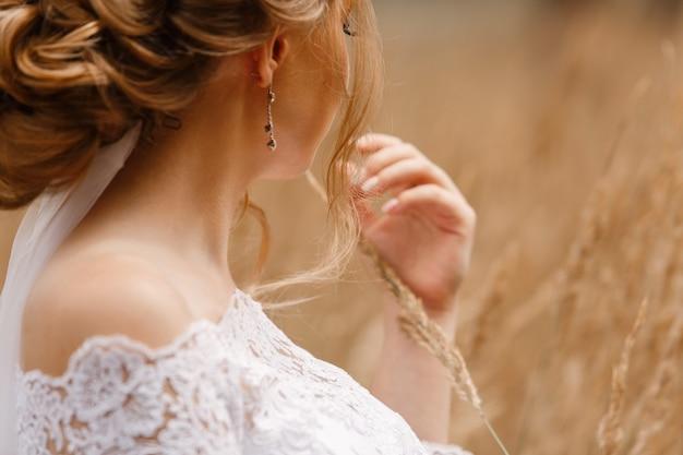 Zartes porträt der braut im weißen kleid draußen auf weizenfeld. hochzeitstag. stilvolle frau mit einem schönen ausschnitt und bloßen schultern mit seitenansicht der frisur. mädchen mit weizenähren in der hand