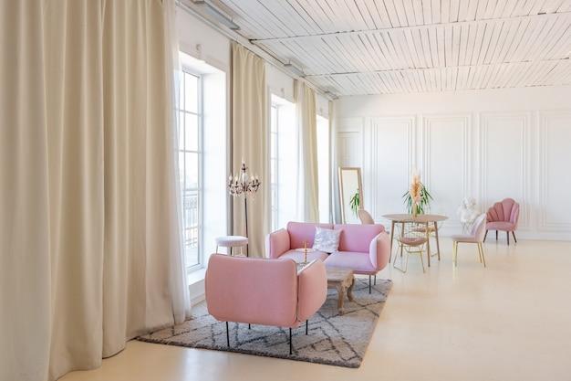 Zartes und gemütliches helles interieur des wohnzimmers mit modernen stilvollen möbeln in pastellrosa und weißen wänden mit stuckleisten bei tageslicht