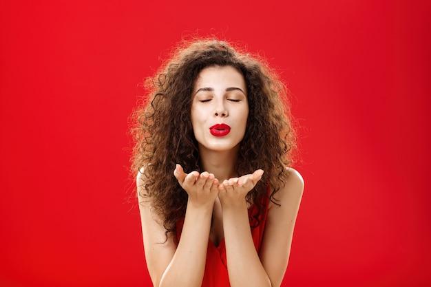 Zartes und sanftes, stilvolles kaukasisches mädchen mit lockiger frisur und rotem lippenstift, der sich mit leichtem lächeln zur kamera beugt, geschlossene augen und handflächen in der nähe von gefalteten lippen, die romantisch einen kuss in die kamera blasen.
