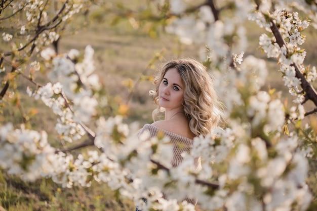 Zartes, verträumtes mädchen mit lockigem blondem haar in blühenden weißen gärten bei sonnenuntergang