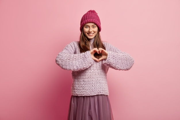 Zartes weibliches mädchen formt herz mit händen über brust, drückt liebe und sympathie aus, trägt rosa kopfbedeckung