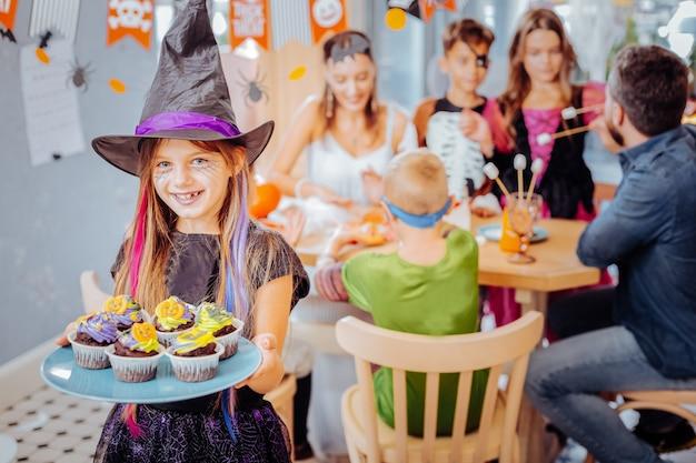 Zaubererhut. lächelndes mädchen, das halloween-zaubererhut hält platte mit feier cupcakes anlässlich des geburtstages trägt