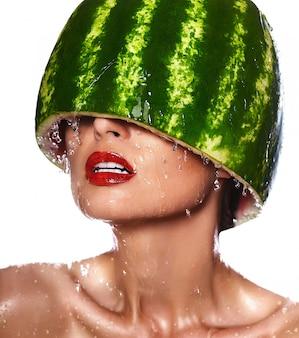 Zaubernahaufnahmeporträt des schönen sexy modells der jungen frau mit wassermelone auf kopf mit wassertropfen