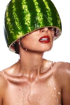 Zaubernahaufnahmeporträt des schönen sexy modells der jungen frau mit wassermelone auf kopf