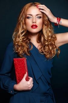 Zaubernahaufnahmeporträt des schönen sexy stilvollen blonden kaukasischen modells der jungen frau mit hellem make-up, mit den roten lippen, mit perfekter sauberer haut mit buntem zubehör im blauen klumpen