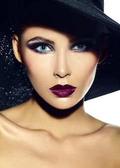 Zaubernahaufnahmeporträt des schönen sexy stilvollen modells der jungen frau mit hellem make-up mit den roten lippen mit perfekter sauberer haut im zufälligen stoff im hut