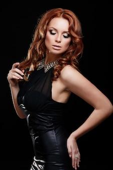 Zauberporträt des stilvollen kaukasischen modells der jungen frau der schönen sexy rothaarigen mit hellem make-up, wenn das perfekte sauber ist, im schwarzen kleid