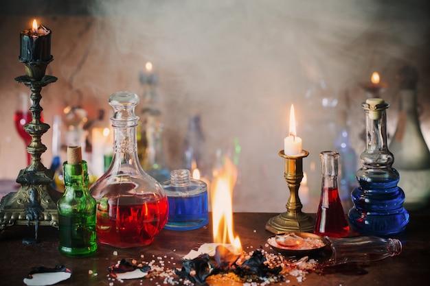 Zaubertrank, alte bücher und kerzen auf dunklem hintergrund