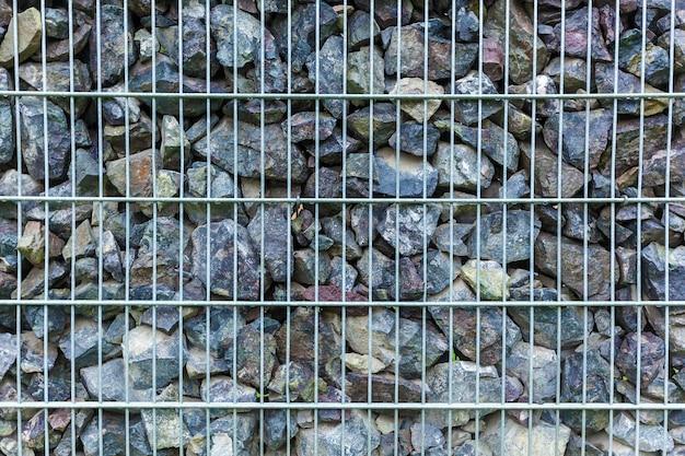 Zaun aus granitstücken und metallgittern
