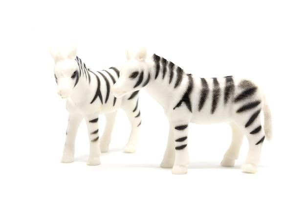 Zebramodell lokalisiert auf weißem hintergrund, tier spielt plastik