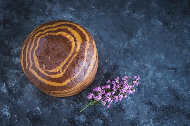 Zebraschwammkuchen auf marmorhintergrund mit heideblumenblumendekoration