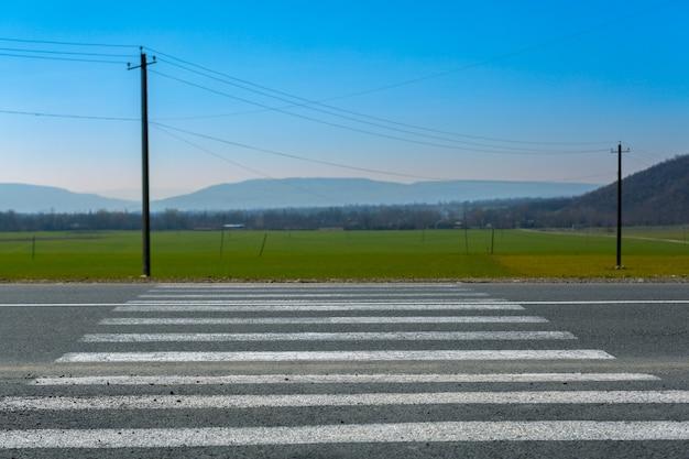 Zebrastreifen auf der landstraße mit grünem feld im hintergrund, sicherer bürgersteig mit fußgängerüberweg. blick auf das feld mit berg und zebrastreifen auf dem asphalt.