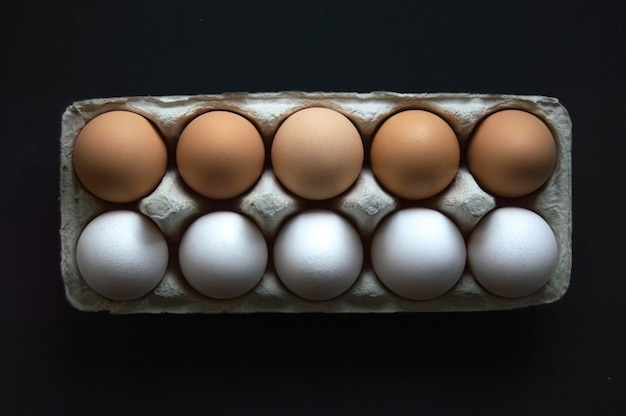 Zehn eier in zwei farben in einem tablett auf einem dunkelschwarzen hintergrund flach draufsicht