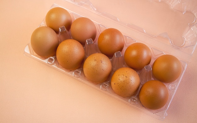 Zehn eier mit brauner schale in plastikbox, auf pastellfarbenem hintergrund