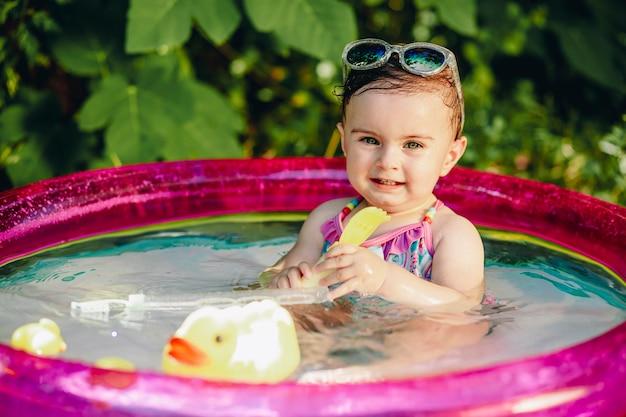 Zehn monate altes baby, das die wärme des sommers in ihrem pool mit gelbem gummientenspielzeug genießt