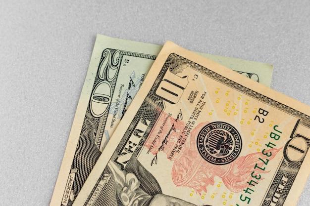 Zehn und zwanzig dollar auf grauem hintergrund. papiergeld. usa-banknoten