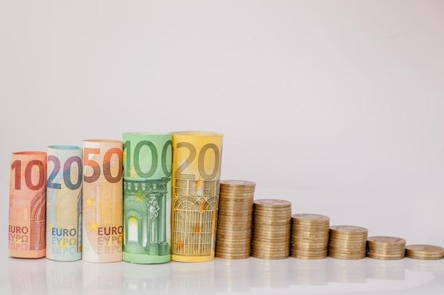 Zehn, zwanzig, fünfzig, einhundert, zweihundert und münzen euro rollten banknoten auf weiß