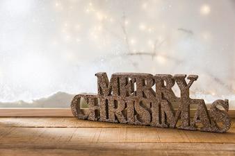 Zeichen der frohen Weihnachten auf hölzerner Tabelle nahe Bank des Schnees und der feenhaften Lichter