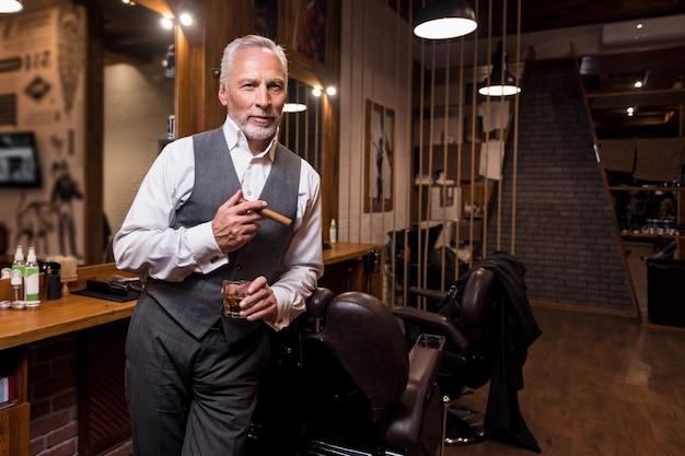 Zeichen des status. porträt des hübschen bärtigen älteren geschäftsmannes, der whiskyglas mit zigarre am friseursalon steht und hält.