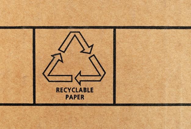 Zeichen für recycelbares papier, gedruckt auf recyceltem karton. nahaufnahme.