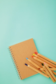 Zeichenstift mit einem notizbuch auf blau