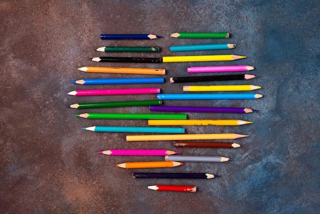 Zeichenstiftherz - herzform gemacht von farbigen bleistiften auf steinhintergrund. valentinstag