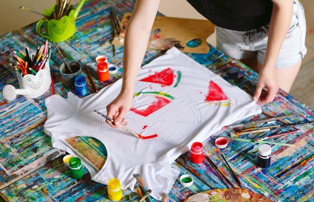 Zeichnen auf kleidung. mädchen zeichnet auf ein weißes t-shirt.